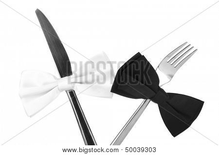 Black and white bow ties  on fork and knife, isolated on white