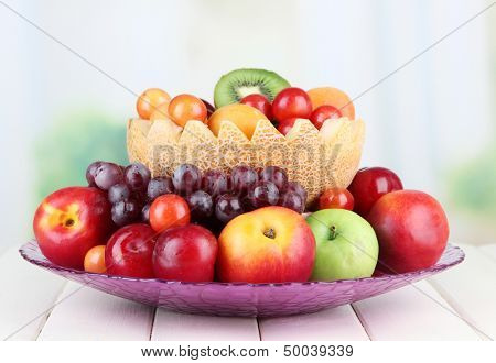 Assortment of juicy fruits on wooden table, on bright background