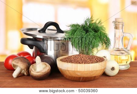 Ingredients for cooking buckwheat on table in kitchen