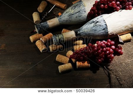 Old bottles of wine, grapes and corks on wooden background