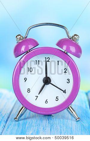 Alarm clock on table on blue background