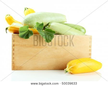 Raw yellow and green zucchini in wooden crate, isolated on white