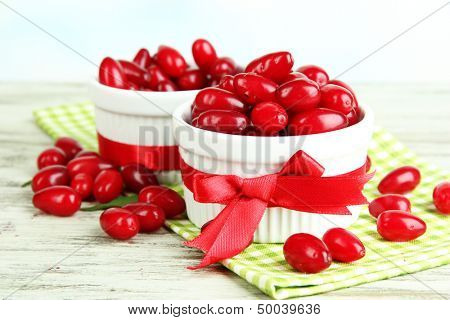 Fresh cornel berries in white cups on wooden table