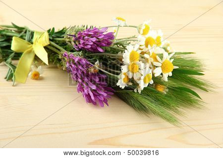 Wild flowers and green spikelets, on wooden background