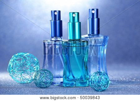 Women perfume in beautiful bottles on blue background