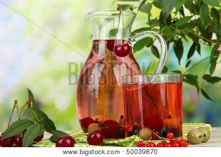 Pitcher and glass of compote with summer berries on natural background
