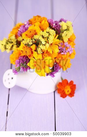 Bouquet of marigold flowers in watering can on wooden table close-up