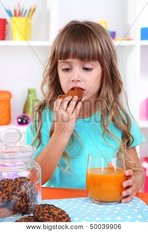 Little girl eating cookies and drinking juice sitting at table in room on shelves background