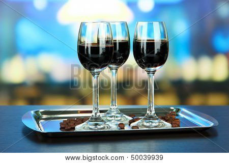 Glasses of liquor on tray,  on bright background