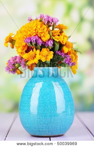 Bouquet of marigold flowers in vase on wooden table on natural background