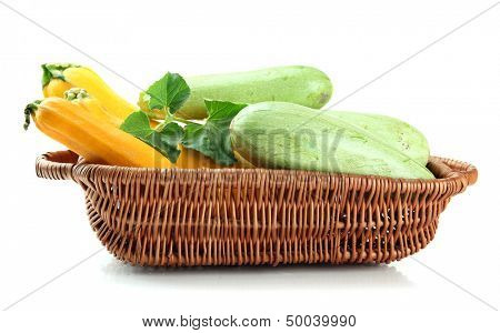 Raw yellow and green zucchini in wicker basket, isolated on white