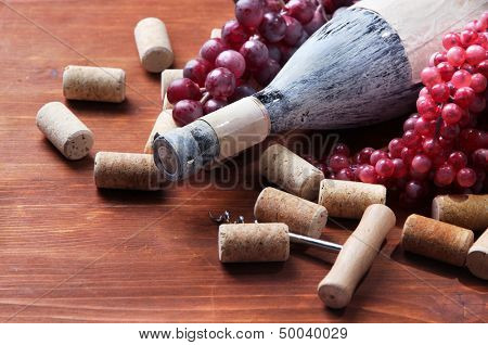 Old bottle of wine, grapes and corks on wooden background