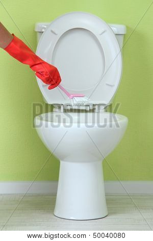 Woman hand with brush cleaning a toilet bowl in a bathroom
