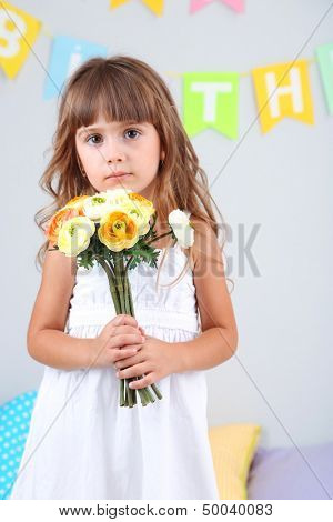 Little girl with flowers in room on grey wall background