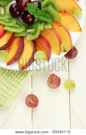 Assortment of sliced fruits on plate, on white wooden table