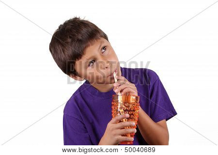 Young boy drinking from orange glass