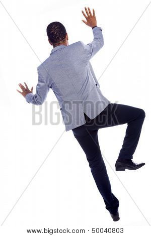 Young businessman climbing a wall, isolated over a white background