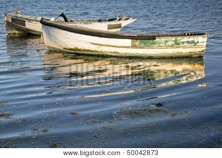 Old Fishing Boats Reflected In Calm Water During Summer Sunset