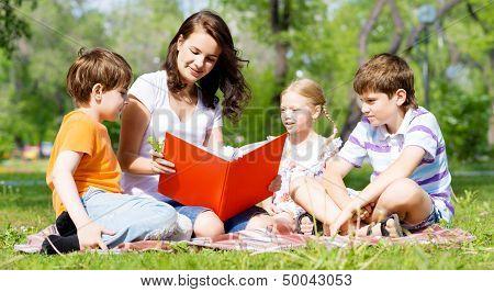 teacher reads a book to children in a summer park
