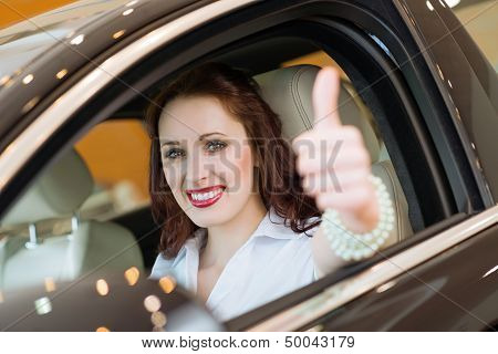 young woman in a car and showing a thumbs up