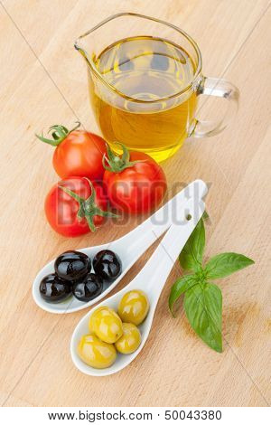 Olives, tomatoes and basil on wood table