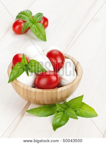 Mozzarella cheese with cherry tomatoes and basil on white wood table