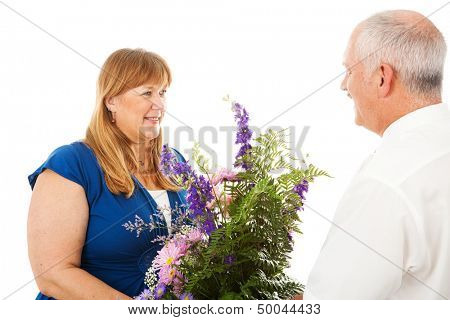 Happy wife receives flowers from her devoted husband.  Isolated on white.