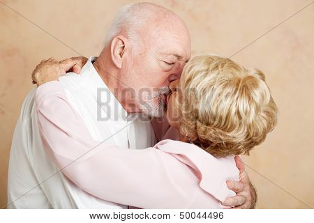 Senior couple in their eighties exchanging a passionate, romantic kiss.