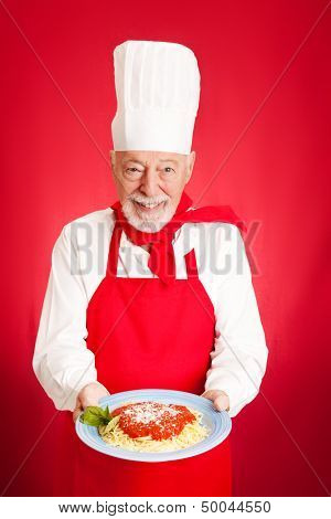 Handsome Italian chef cooks spaghetti marinara.  Red background.
