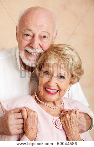 Head and shoulders portrait of a happy, beautiful senior couple.