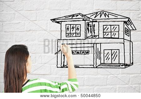 Woman Draw House On Brick Wall