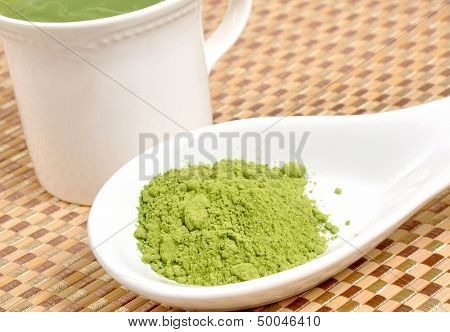 Matcha green tea on a spoon by a cup of green tea