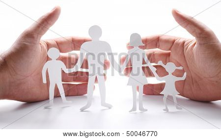 Cardboard figures of the family on a white background. The symbol of unity and happiness. Hands gently hug the family.