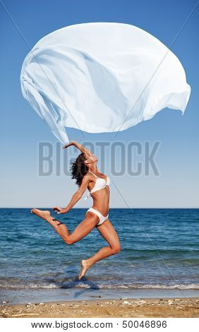 Sexy athletic brunette jumping on the beach with a large white cloth.