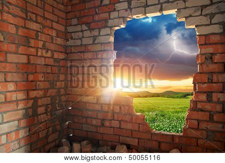 Broken bricks wall and landscape. Conceptual composition.