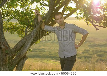 Guy under tree on field