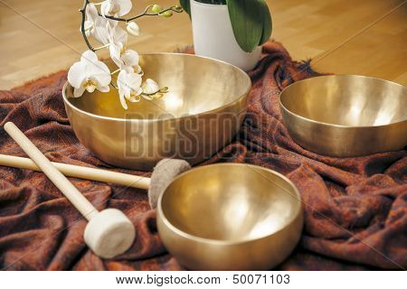 An image of some singing bowls and a white orchid