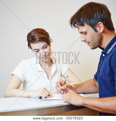 Man filling out patient form at doctors office with the help of a doctors assistant