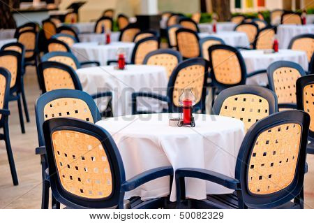 Empty tables in a summer cafe in the morning standing in a row