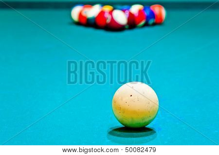 white cue ball close-up on a pool table covered with green baize