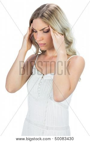 Sensual blonde massaging her temples on white background