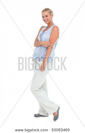 Blonde woman looking at camera and smiling on white background