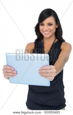 Smiling elegant brown haired model looking at her tablet pc on white background