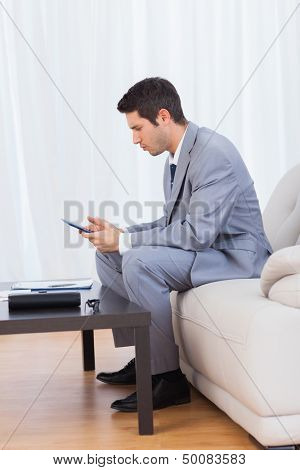 Businessman sitting on sofa texting message with his mobile phone at office