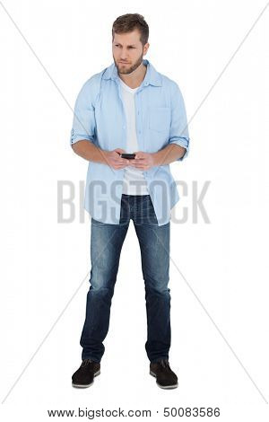Serious man on white background looking away and holding a phone