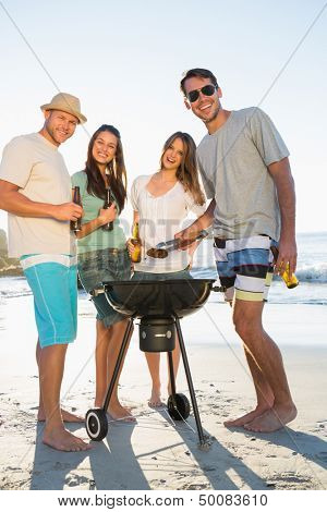 Happy friends on the beach looking at camera while having barbecue together