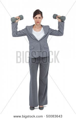 Businesswoman posing with dumbbells on white background