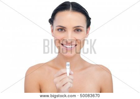 Cheerful young model holding nail clippers on white background