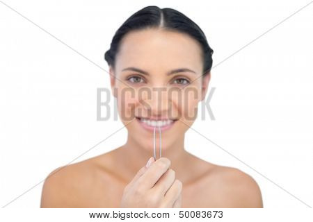 Cheerful young brunette with tweezers on white background
