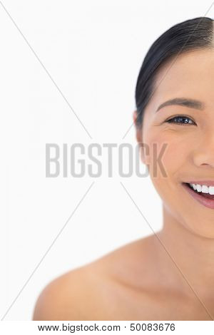 Half face of smiling natural model on white background